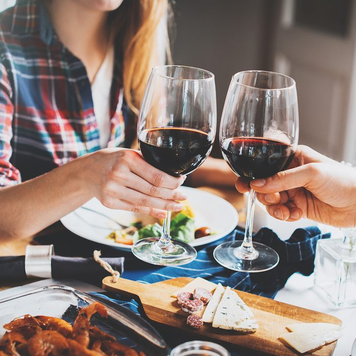 Young romantic couple celebrating with glasses of red wine