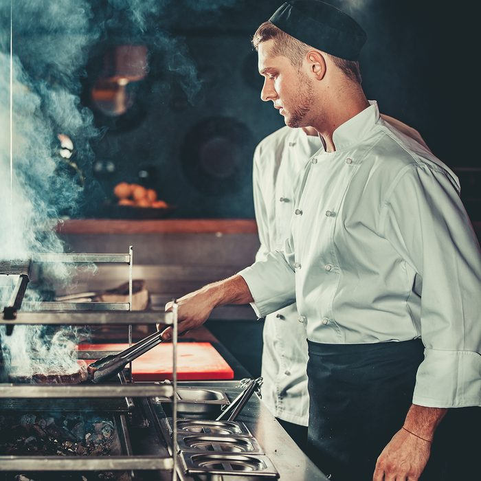 Young white chef in black apron and hat standing near the brazier whith coals.