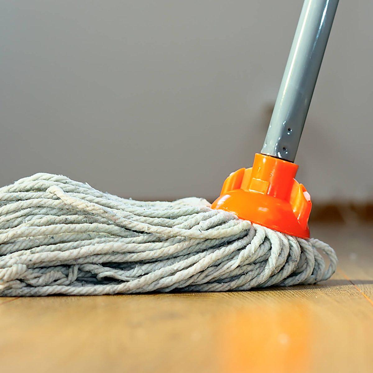 cleaning wooden floor with orange wet mop