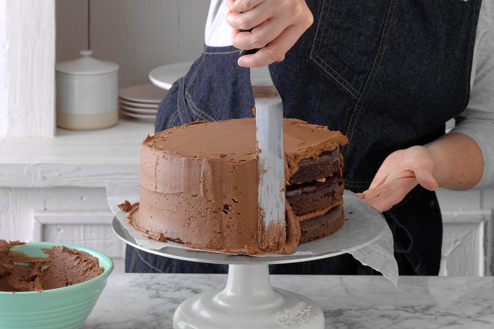 Frosting a chocolate cake