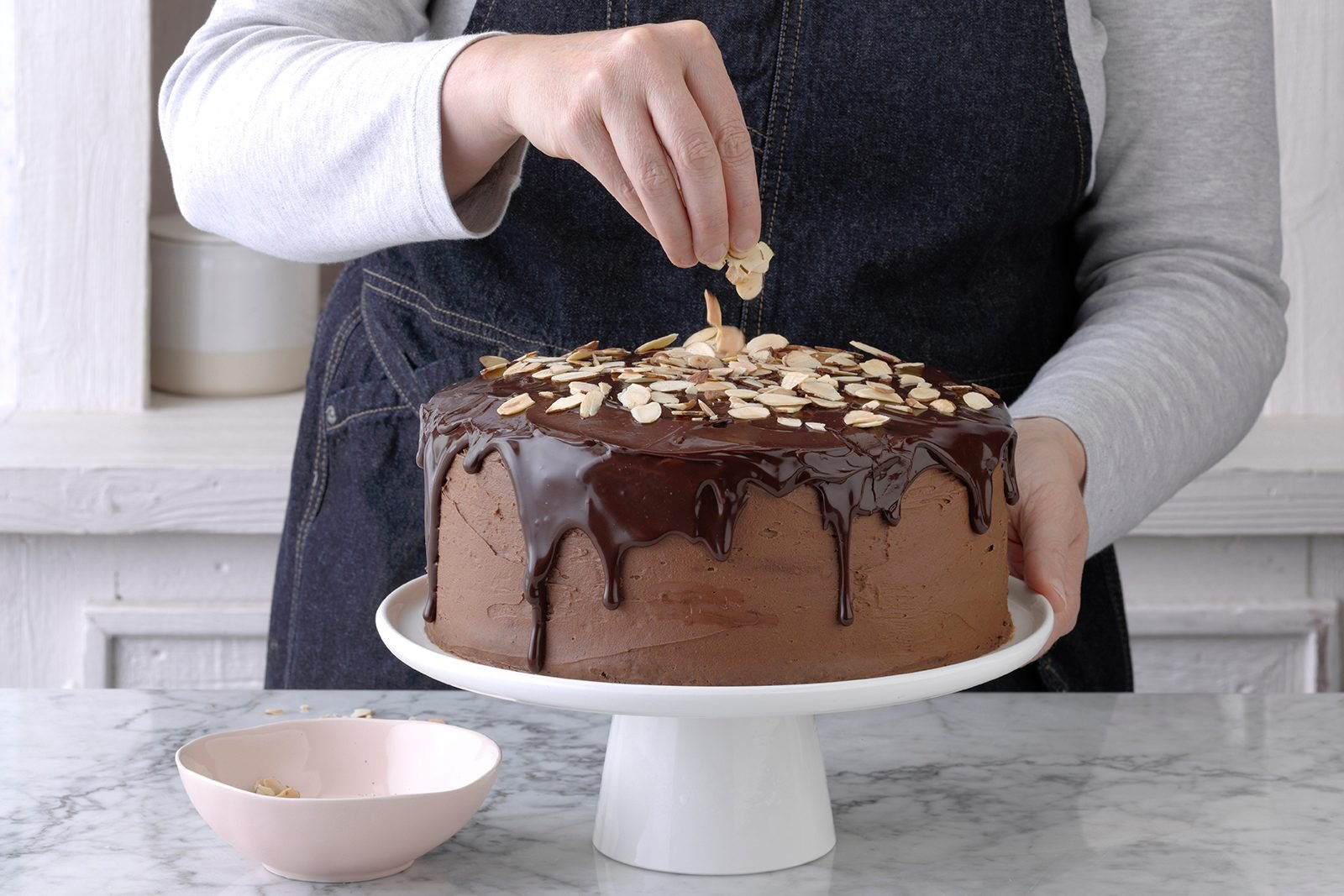 Topping chocolate ganache cake with almonds
