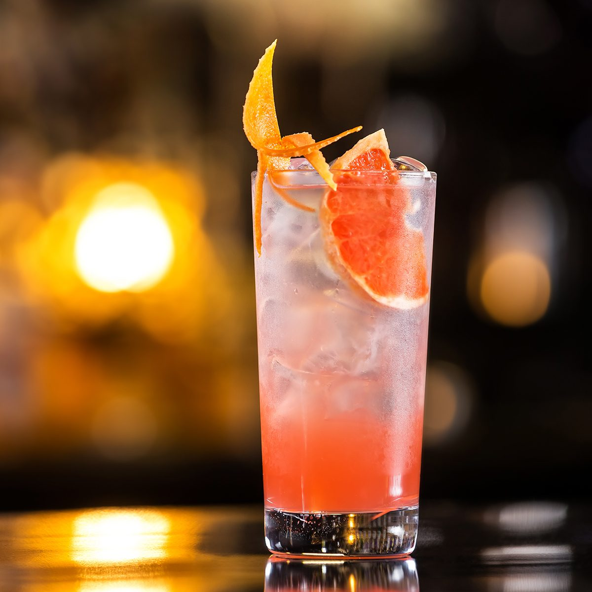 Closeup glass of greyhound cocktail decorated with grapefruit at bright bar counter background.