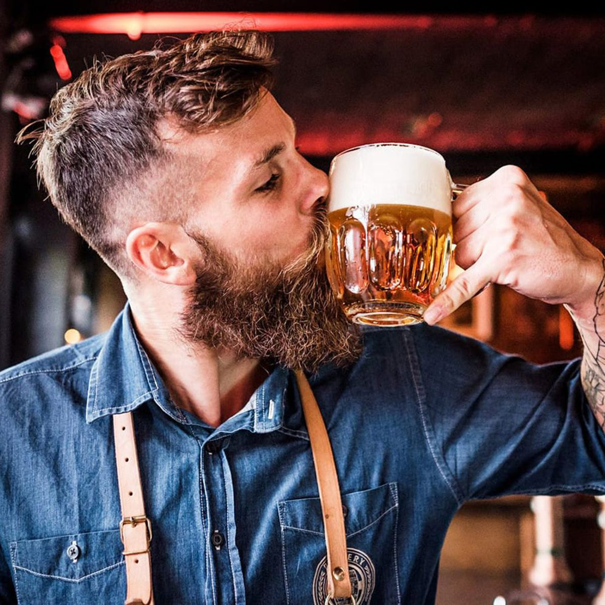 Man kissing a glass of Pilsner Urquell