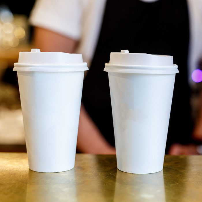 Barista making two cappuccinos in a paper cup to go, cups on a counter