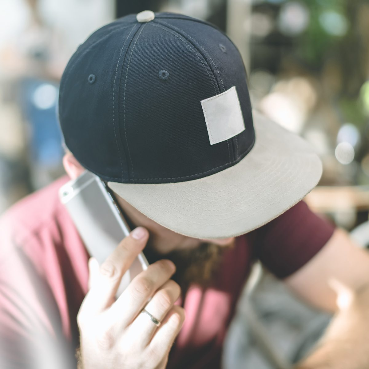 Closeup of a baseball cap with space for text. A man in a cap with a visor sitting with his head down and talking on the phone. Man uses the gadget.