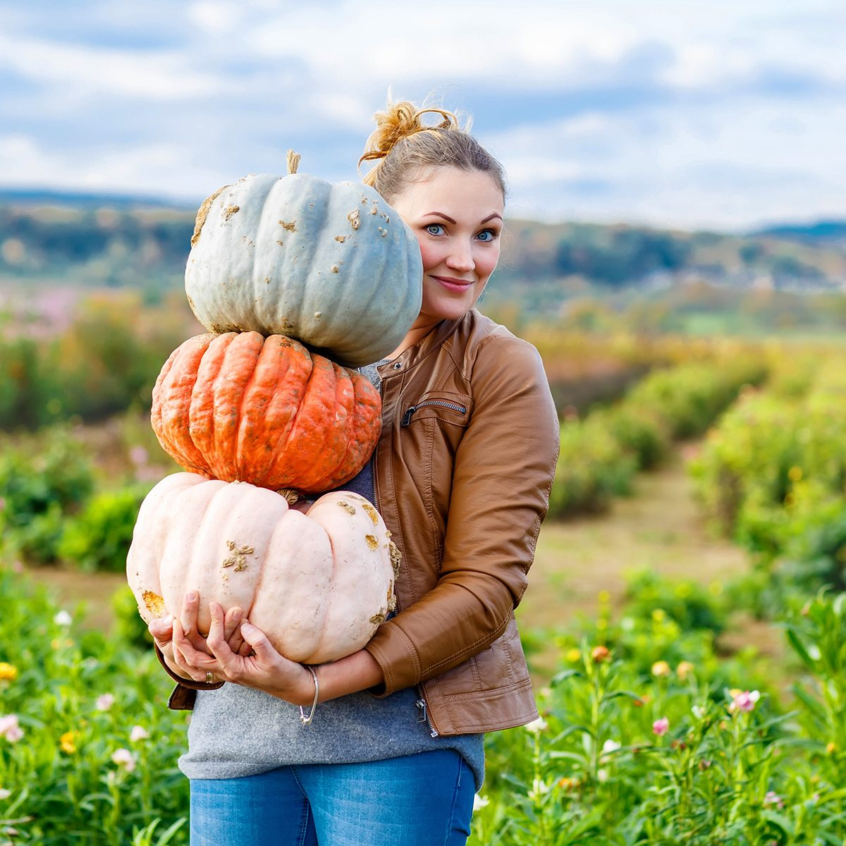 Beautiful young woman with three huge different pumpkins on a farm or patch.