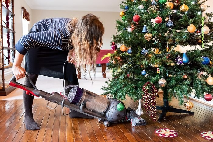 Young woman cleaning with vacuum cleaner, vacuuming under Christmas Tree needles