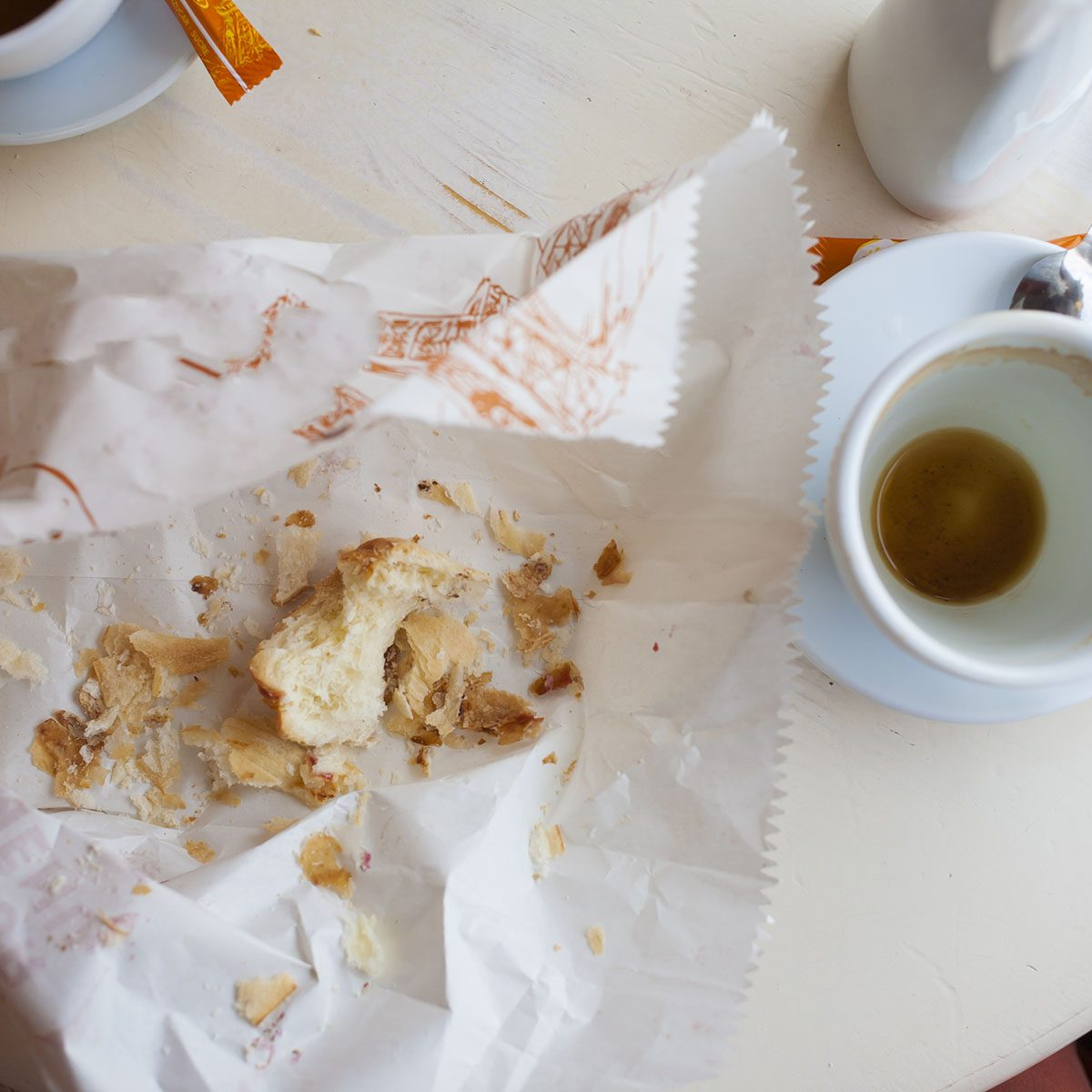 Empty coffee Cup and the remains of biscuits are on the table.