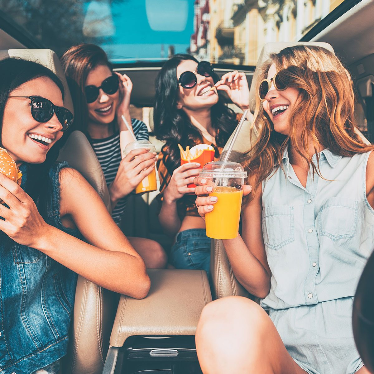 Enjoying their lunch in the car. Four beautiful young cheerful women looking at each other with smile and eating take out food while sitting in car