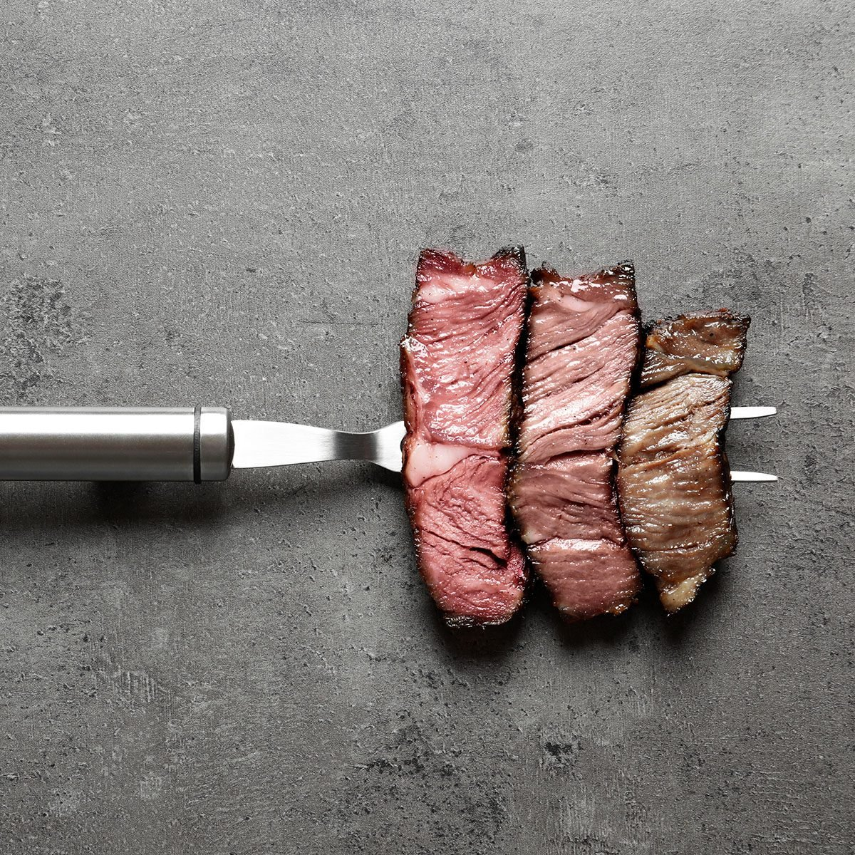 Fork with pieces of delicious barbecued meat on gray background