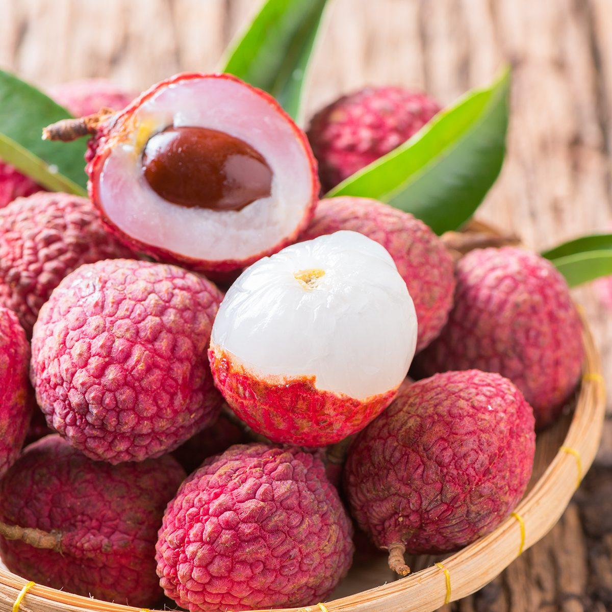 fresh organic lychee fruit on bamboo basket and old wood background