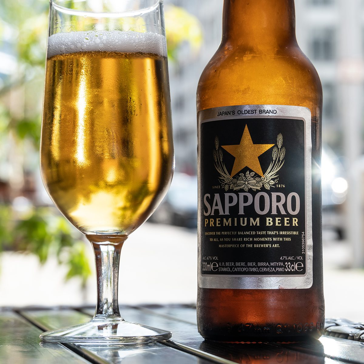 A glass full with beer next to a bottle of Sapporo Premium Beer on the table