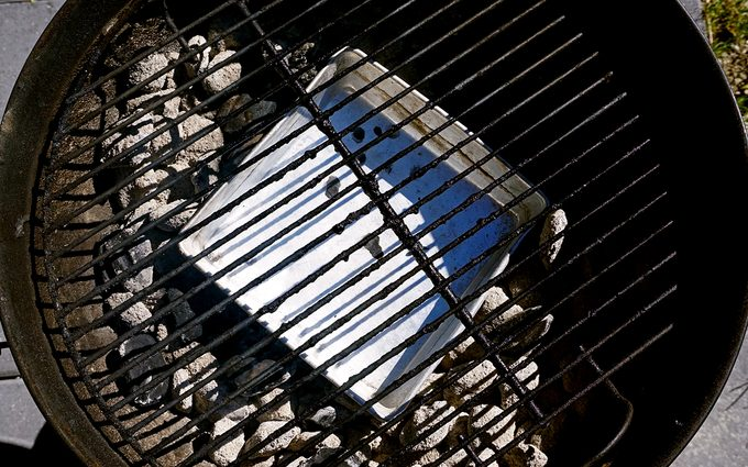 arranging the coals and drip pan for grilled thanksgiving turkey