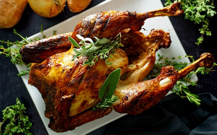whole grilled turkey on a platter with herbs