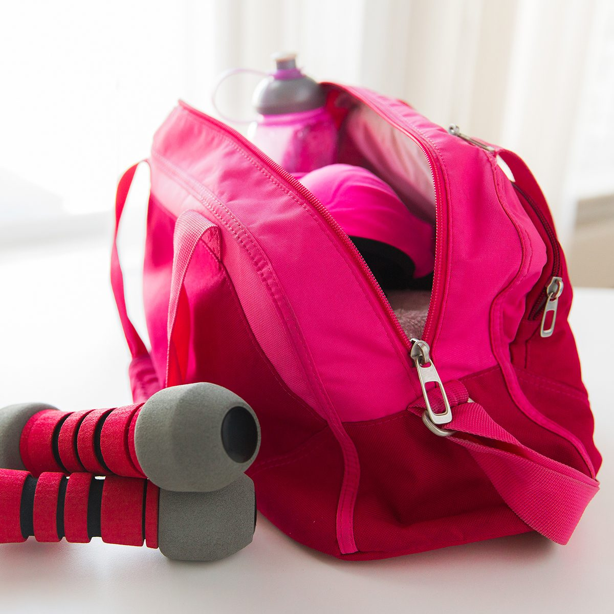 sport, fitness, healthy lifestyle and objects concept - close up of female sports stuff in bag and dumbbells