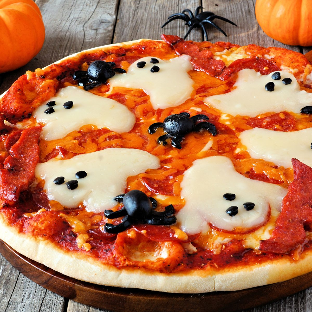 Halloween pizza with ghosts and spiders, close up on a rustic wood background