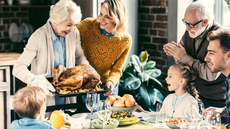 beautiful grandmother carrying turkey for family on thanksgiving dinner