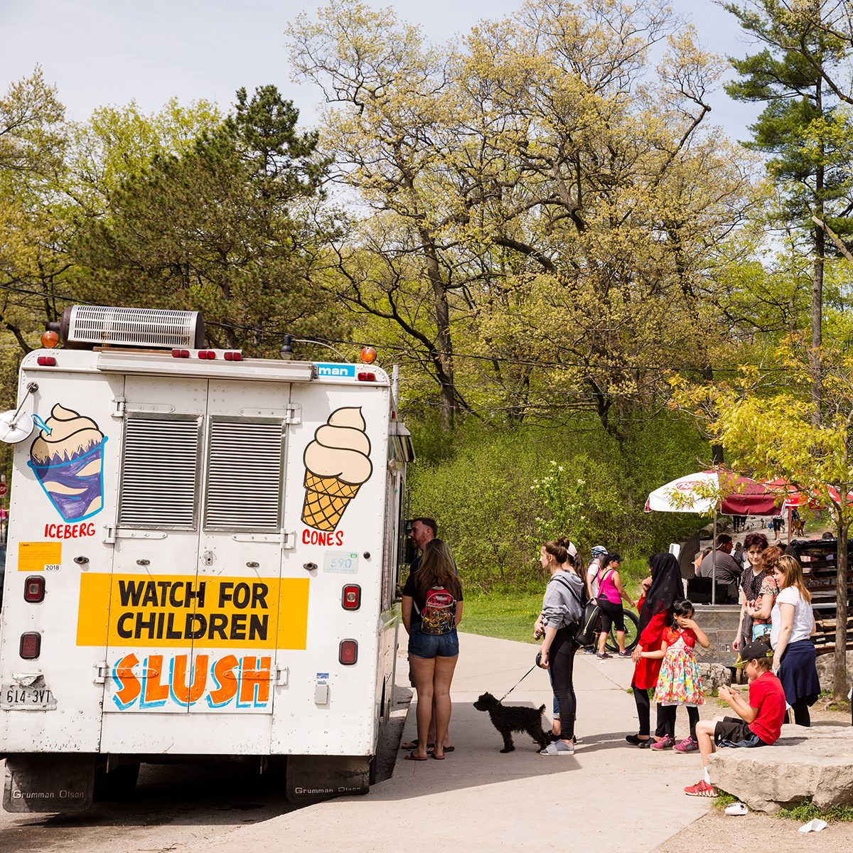 PEOPLE WAIT IN LONG LINE FOR ICE CREAM TRUCK AT HIGH PARK.