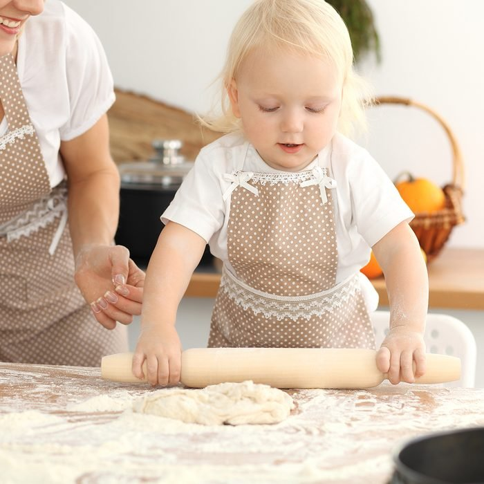 Little girl and her blonde mom in beige aprons playing and laughing while kneading the dough in kitchen.