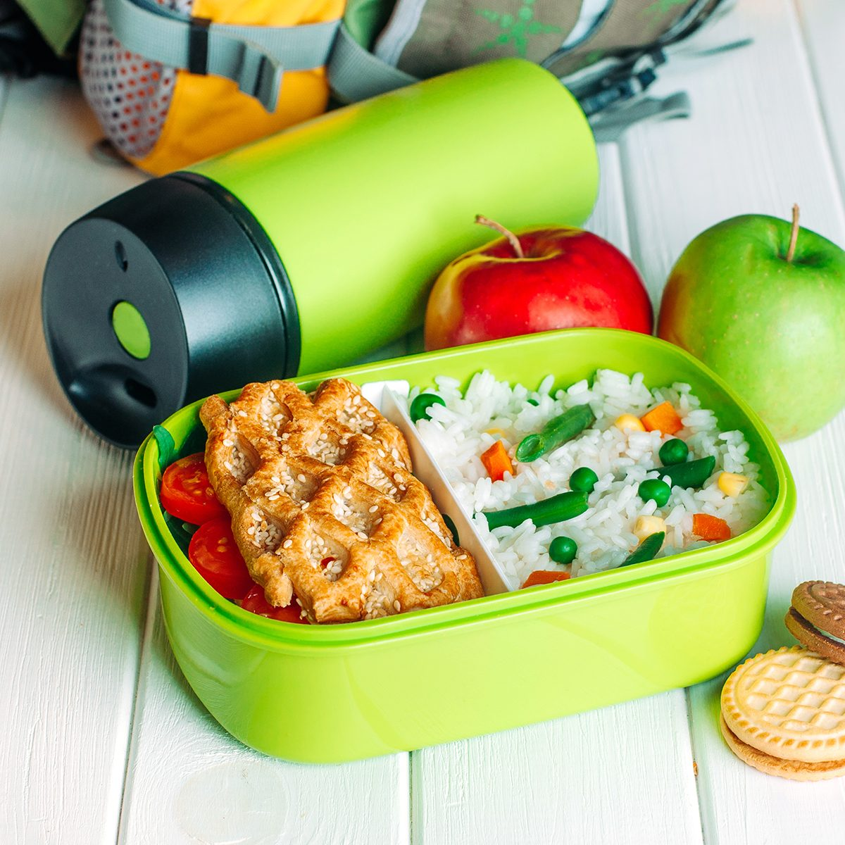 Lunch box filled with rice and sandwich near thermos, fresh apples and biscuits in front of kids school backpack on white wooden background