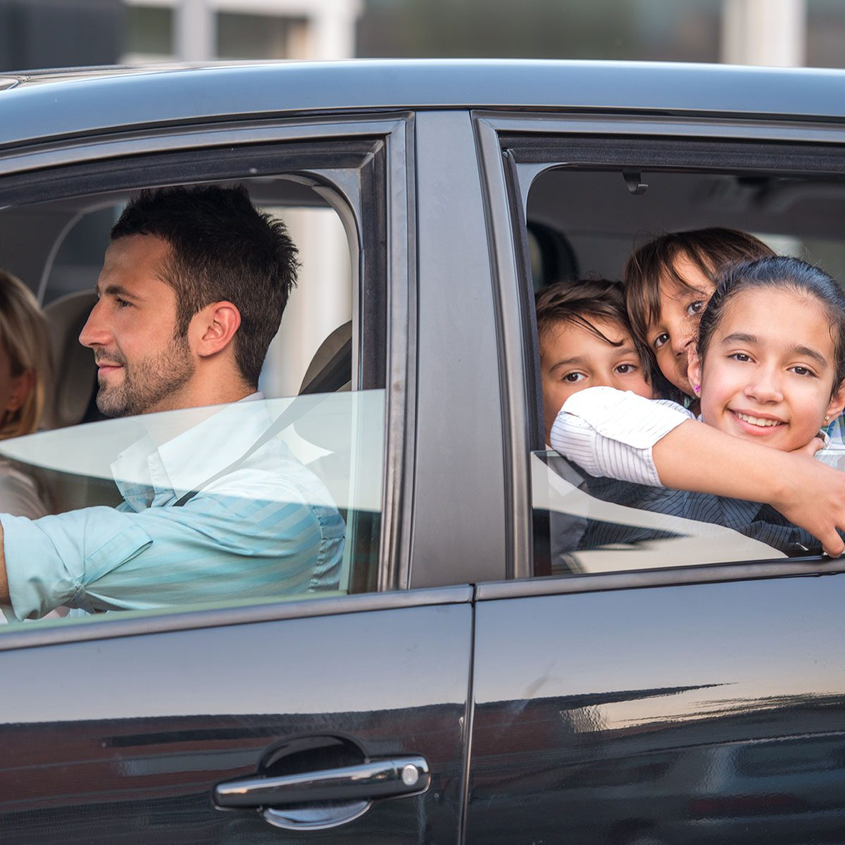 Outside view of a beautiful family driving in automobile
