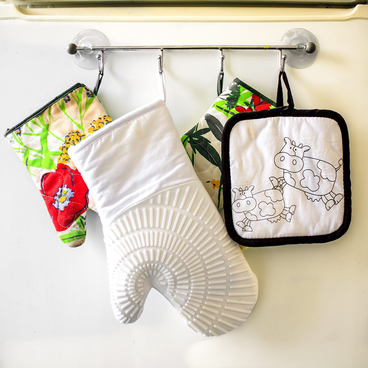 Oven gloves hanging in a row on the kitchen fridge