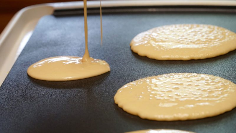 Pancake batter baking mix being poured from a bowl onto a hot electric griddle cooking delicious breakfast meal for a family