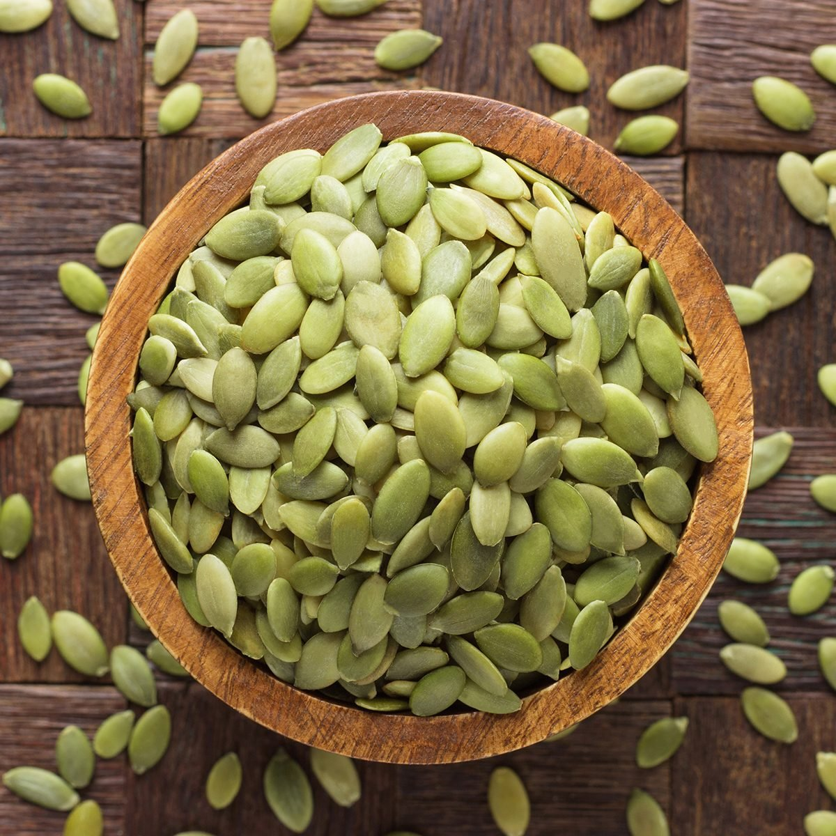 pumpkin seeds peeled in bowl on wooden table background.