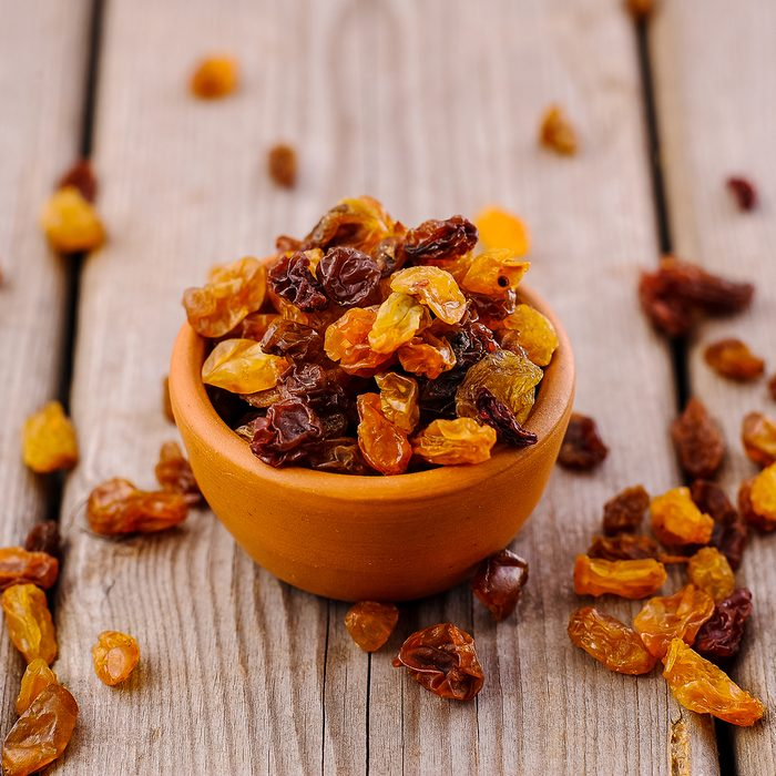 bowl of raisins. raisins on a wooden background.
