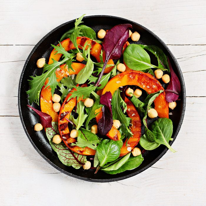 Roasted pumpkin salad with chick pea and fresh herbs overhead a white wooden background.