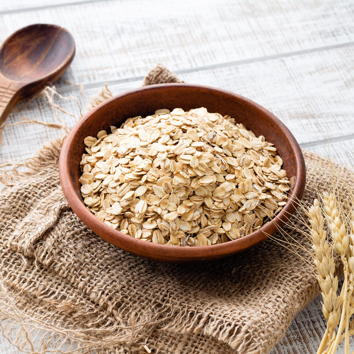 Rolled oats, healthy breakfast cereal oat flakes in bowl on wooden table