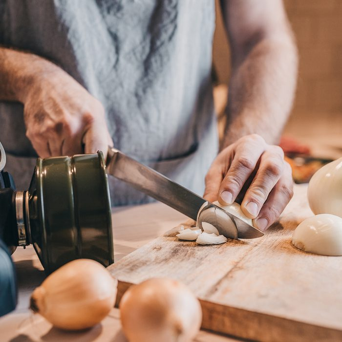 Rough male hands thinly chop the white onion with a knife on a wooden board - a gas mask from tears when cutting onions