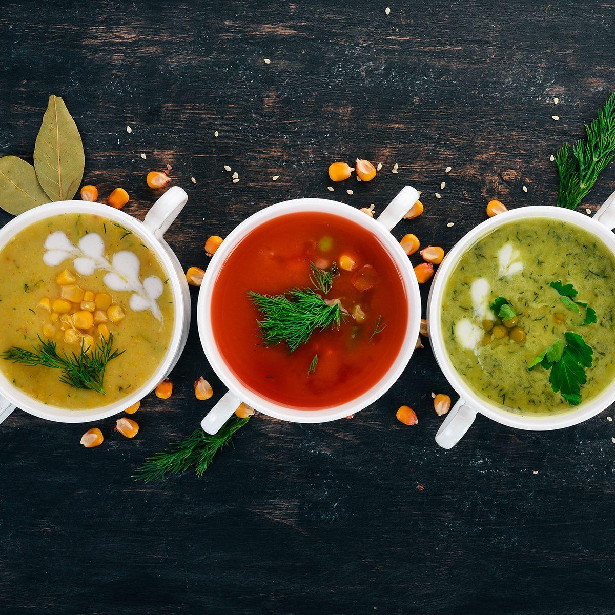 Set of hot, colored vegetable soups. Broccoli soup, corn, tomato soup.