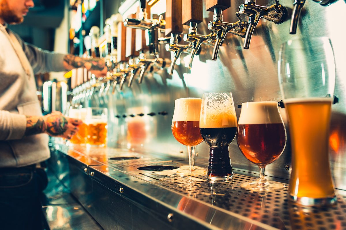 Hand of bartender pouring all types of craft beer on tap.