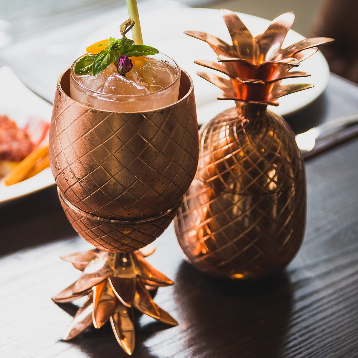 Cocktail served inside copper pineapple cup with dishes in the background. ; Shutterstock ID 1080759941; Job (TFH, TOH, RD, BNB, CWM, CM): TOH