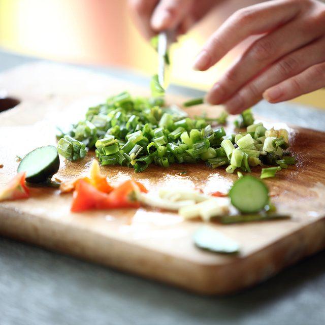 Closeup of Human hands cooking vegetables salad in kitchen; Shutterstock ID 116301946