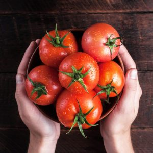 Fresh tomatoes in hands on a wooden background. Harvesting tomatoes. Top view; Shutterstock ID 1167200134; Job (TFH, TOH, RD, BNB, CWM, CM): Taste of Home