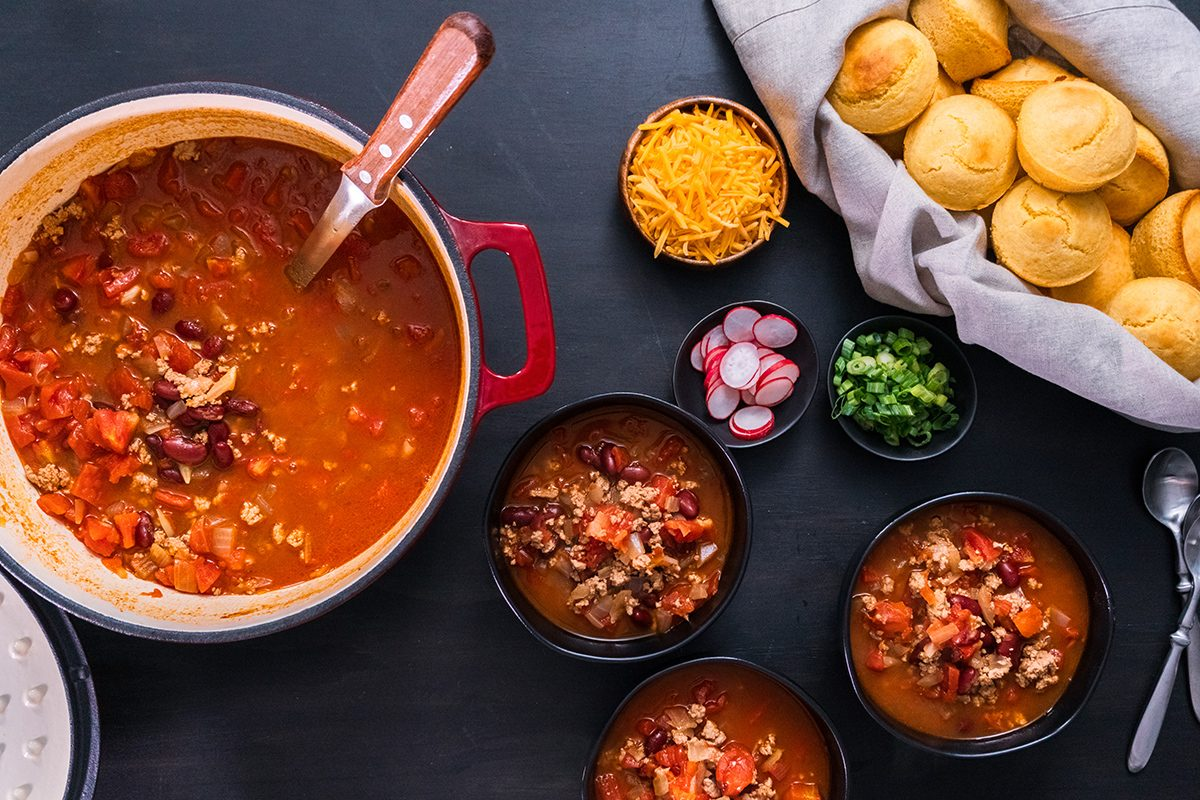 Turkey chili garnished with fresh radishes, green onions and cheddar cheese; Shutterstock ID 1195983994; Job (TFH, TOH, RD, BNB, CWM, CM): Taste of Home