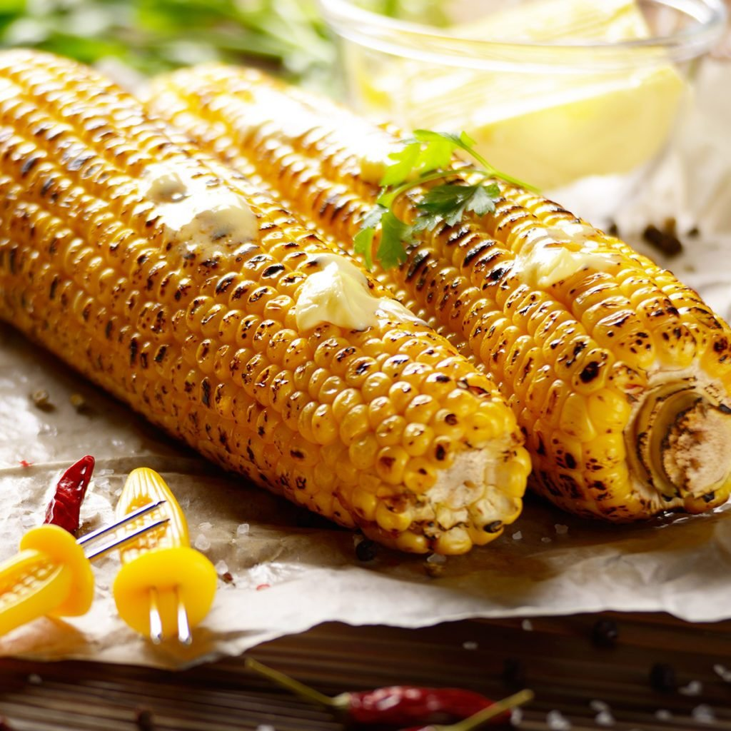 Kitchen table with grilled sweet corn cob under melting butter and greens on baking paper; Shutterstock ID 1250918788; Job (TFH, TOH, RD, BNB, CWM, CM): Taste of Home
