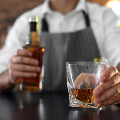 Bartender with glass and bottle of whiskey at counter in bar, closeup. Space for text; Shutterstock ID 1254427798; Job (TFH, TOH, RD, BNB, CWM, CM): Taste of Home