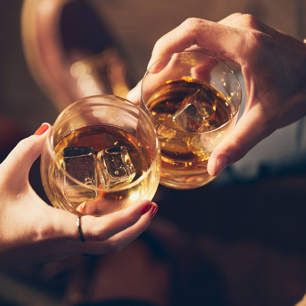 A couple makes a toast with two glasses of whiskey; Shutterstock ID 1280431228; Job (TFH, TOH, RD, BNB, CWM, CM): Taste of Home