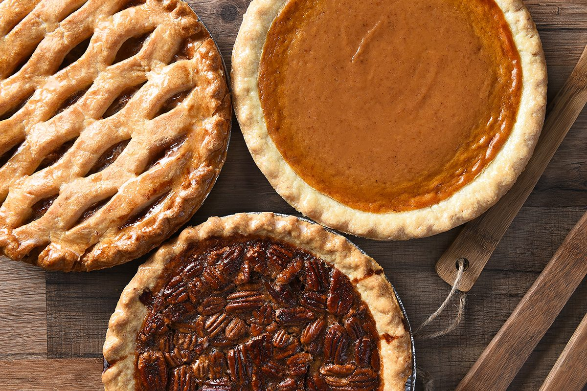 Overhead view of three pies for a Thanksgiving Holiday feast. Pecan, Apple and Pumpkin in horizontal format on wood table; Shutterstock ID 340317356