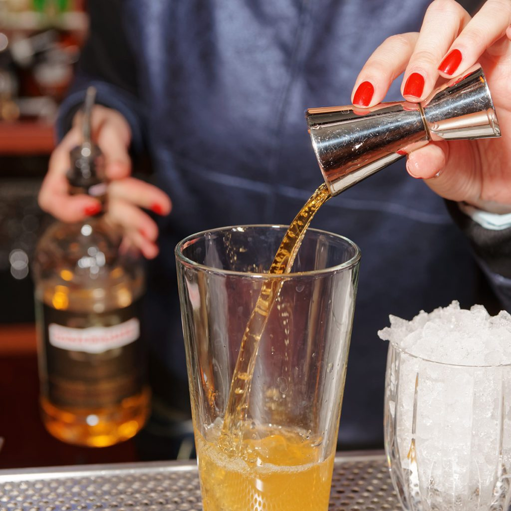 Female bartender is adding whiskey to the mixing glass; Shutterstock ID 369783173; Job (TFH, TOH, RD, BNB, CWM, CM): Taste of Home