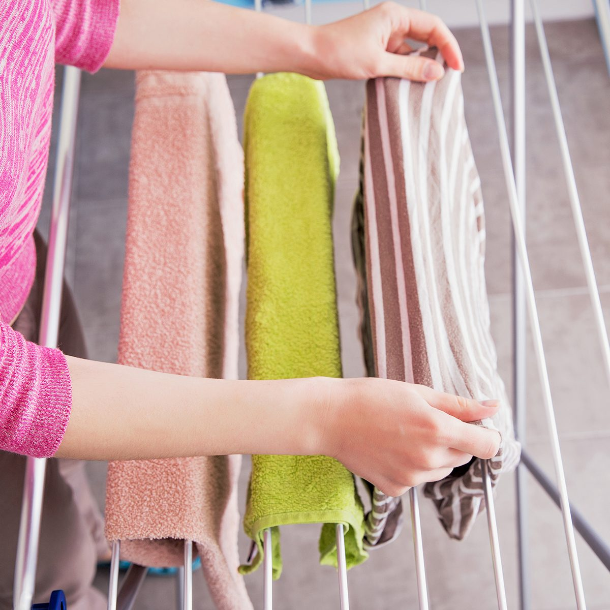A young woman hangs clothes on the dryer for clothes after washing in a washing machine. Device for drying laundry after washing.; Shutterstock ID 637356079; Job (TFH, TOH, RD, BNB, CWM, CM): TOH