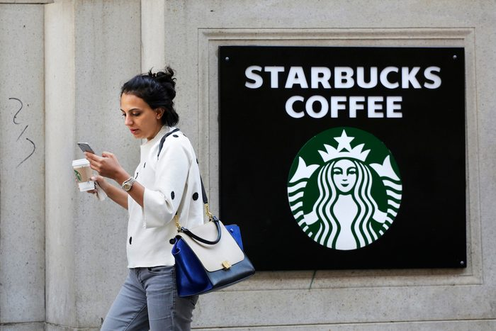 A woman walks out of a Starbucks Coffee with a beverage in hand in New York.