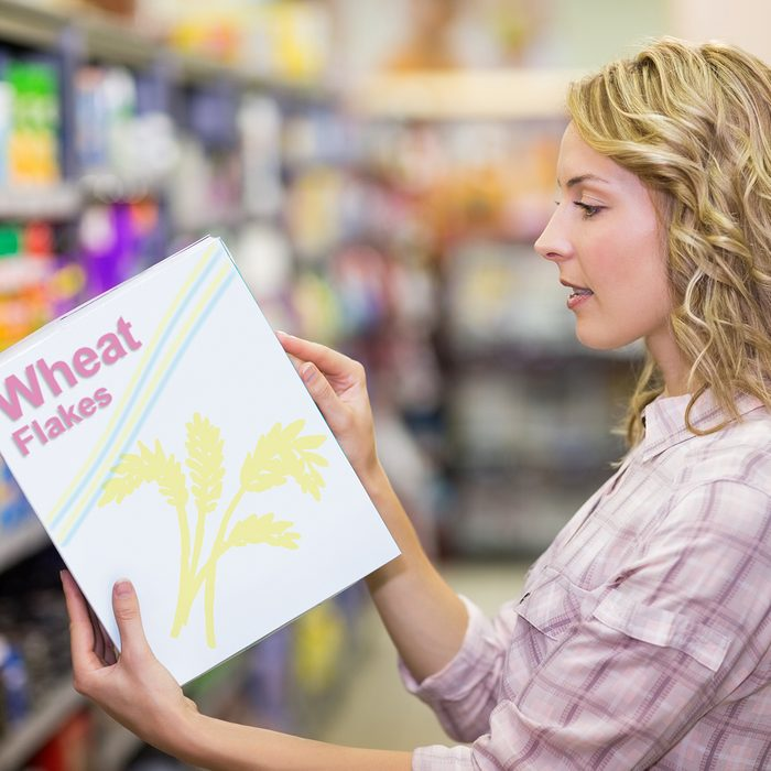 Side view of a pretty blonde woman reading a book in supermarket