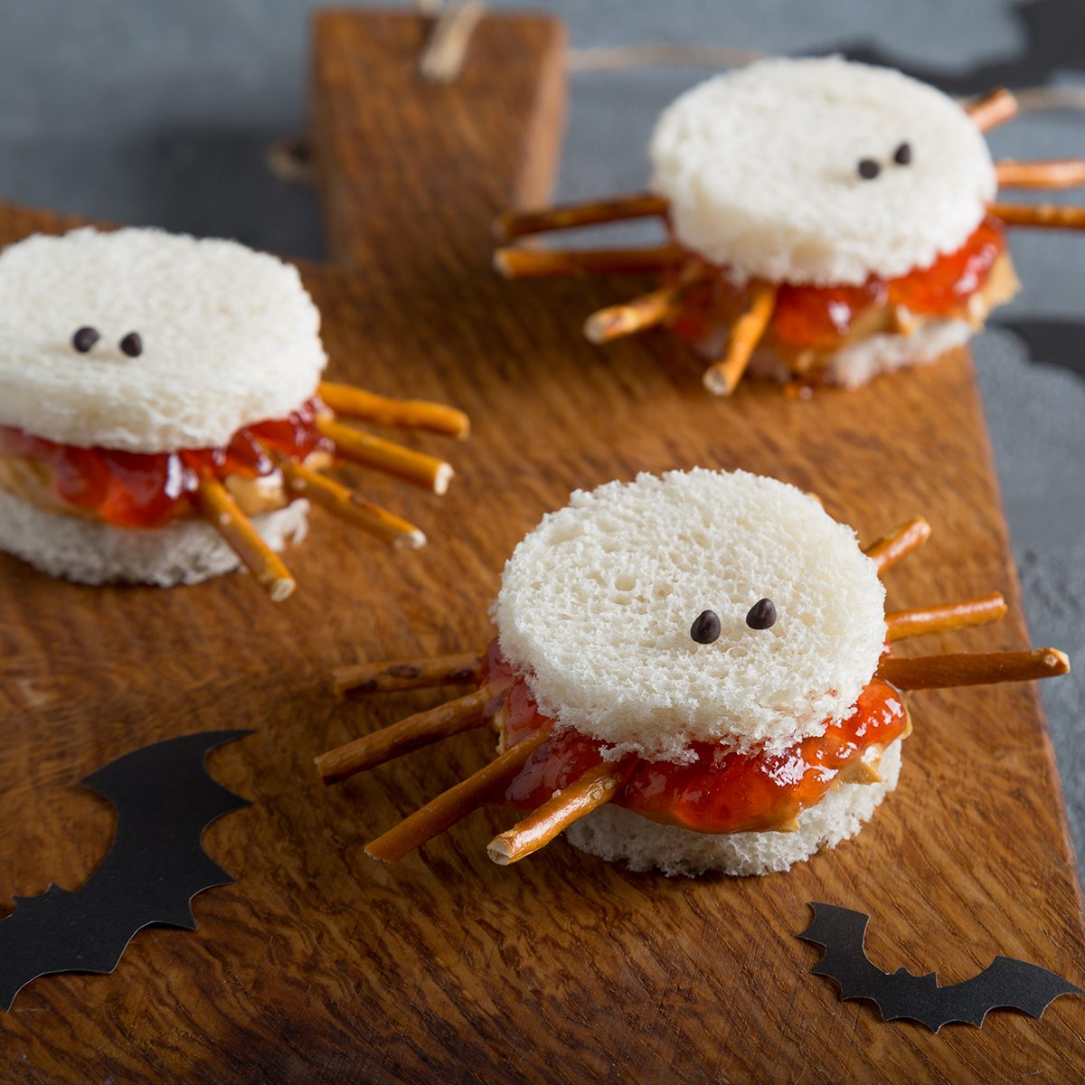 Spooky peanut butter and jelly spider sandwiches with paper bats for halloween on a brown rustic cutting board.