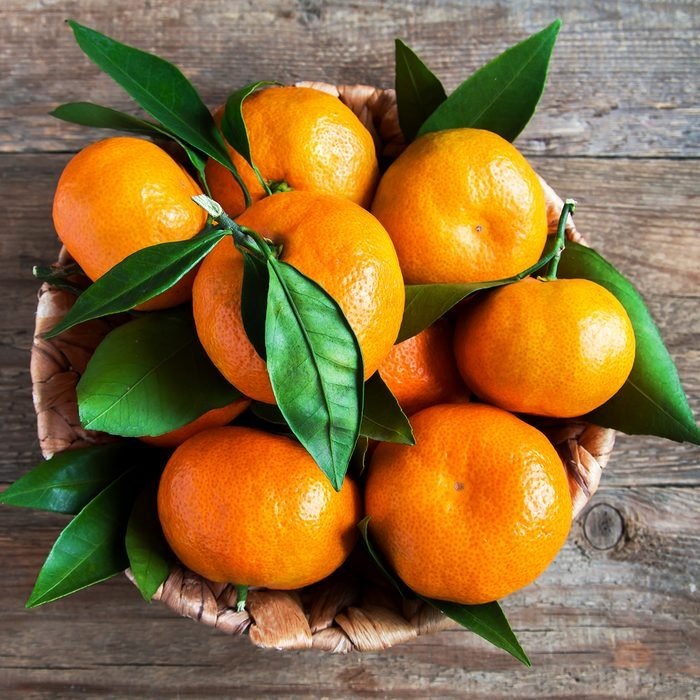 Tangerines (oranges, mandarins, clementines, citrus fruits) with leaves in basket over rustic wooden background