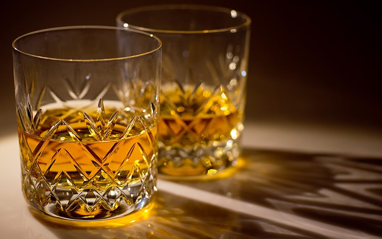 two cut crystal whisky glasses with whisky