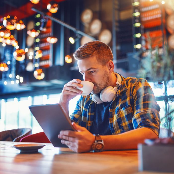 Young handsome Caucasian unshaven man in plaid shirt and with headphones around neck using tablet and drinking espresso while sitting in coffee shop.